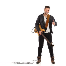 Smiling Guitarist Showing Thum...