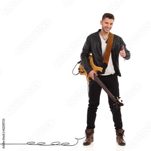 Fotografia Smiling guitarist showing thumb up.