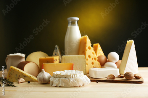 Fotografía  Tasty dairy products on wooden table, on dark background