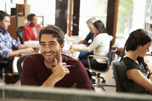Businessman Working At Desk With Meeting In Background