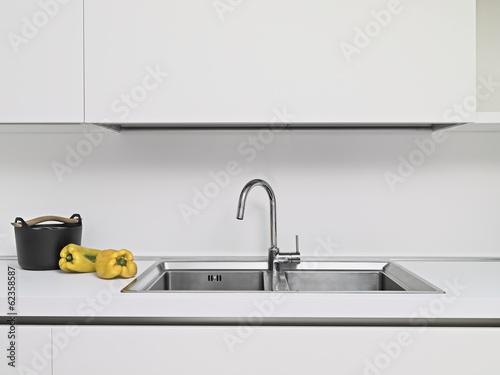 Fotografía  Debido salchichón gialli vicino al lavello nella cucina moderna