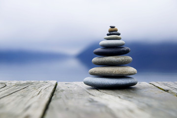 Fototapeta Zen Balancing Pebbles Next to a Misty Lake