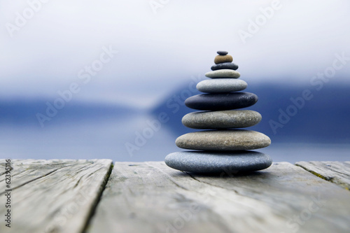 Zen Balancing Pebbles Next to a Misty Lake Poster