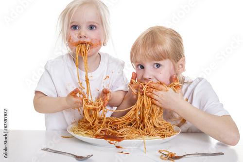 Foto op Canvas Kruidenierswinkel zwei Mädchen essen Spaghetti