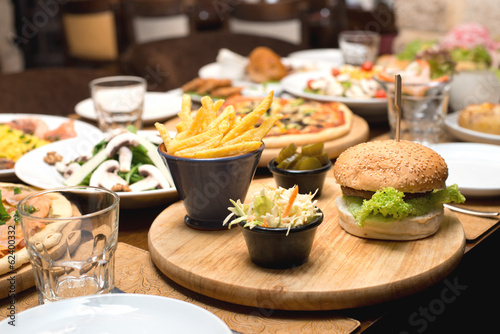 Beef burger and french fries on a table with other food plates © Ramzi