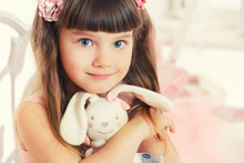 Little Girl With Soft Toy Sitting On A Chair