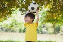 Little Boy Holding Up Football...