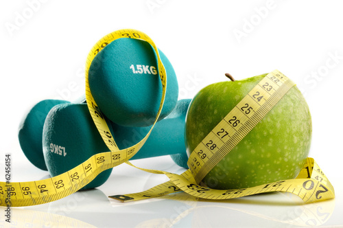 Fotografía  healthy apple, measuring tape and dumbbells isolated