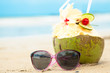 picture of fresh cocnut cocktail and pink sunglasses on tropical