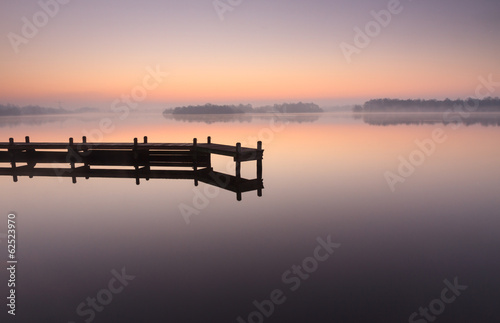 Fotomural  Jetty during a tranquil, foggy dawn at a lake.
