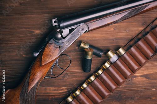 Fototapeta Shotgun with shells on wooden background
