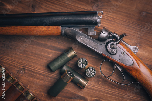 Obraz na plátne Shotgun with shells on wooden background