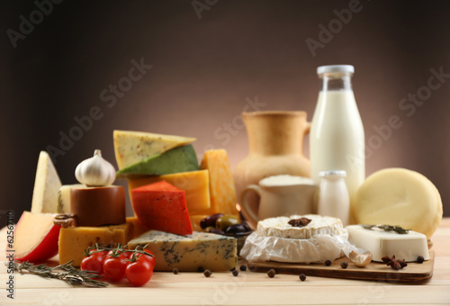 Poster Dairy products Tasty dairy products on wooden table, on dark background