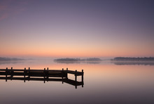 Jetty At A Lake During A Tranquil, Foggy Dawn.