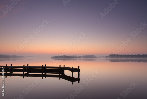 Foto Jetty at a lake during a tranquil, foggy dawn.