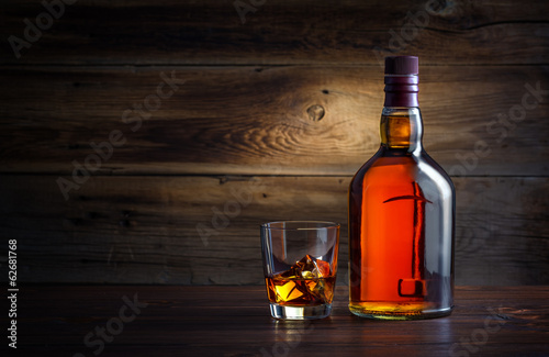 bottle and glass of whiskey with ice on a wooden background Canvas Print