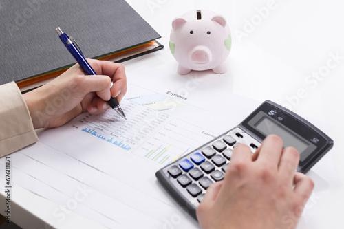 Vászonkép Women calculate expenses with calculator and piggybank