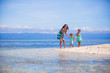 Adorable little girls and young mother have fun on tropical