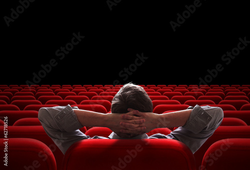 Fotografía  one man sitting in empty cinema or theater auditorium
