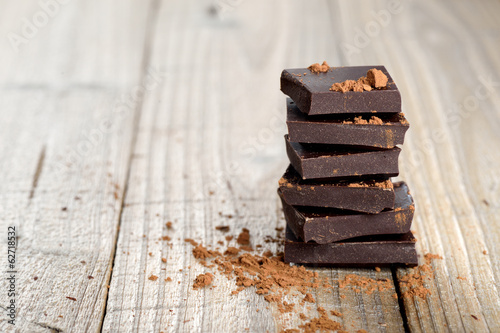Fotografía  Pile of chocolate pieces with cocoa on wooden background