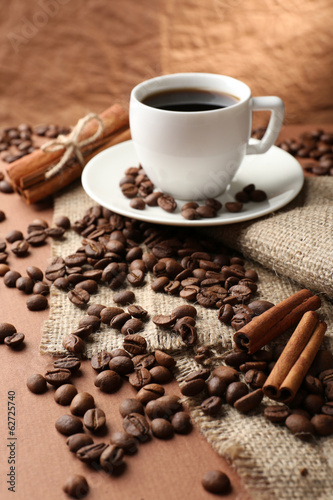 Foto op Canvas Cafe Coffee beans and cup of coffee on table on brown background