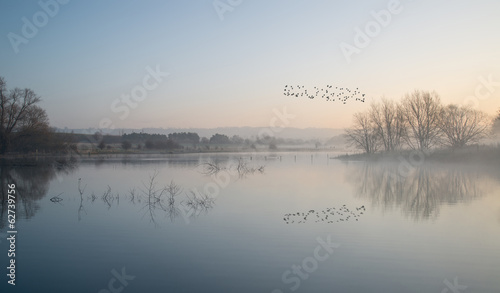 Staande foto Donkergrijs Landscape of lake in mist with sun glow at sunrise