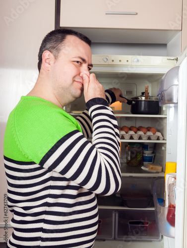 Fotografia, Obraz  Guy looking for something in pan near fridge