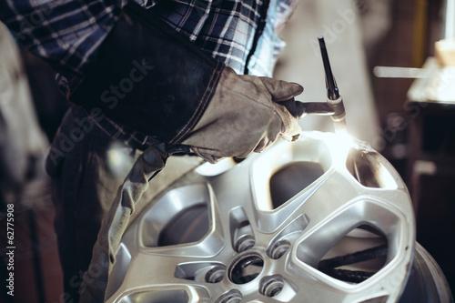 Pinturas sobre lienzo  Alloy wheel repair, closeup of mechanic welding rim