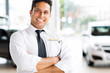 indian vehicle salesman with arms crossed
