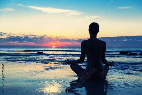 Meditation on the beach. Women sitting in lotus