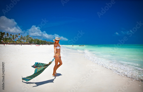 Zanzibar Fashion woman relax on the beautiful tropical beach in Africa.