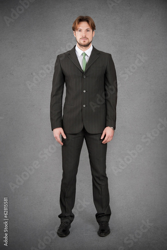 Fotografie, Obraz  Young businessman full body front portrait against grunge backgr