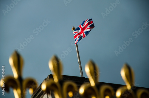 Photo golden fence of buckingham palace with british flag
