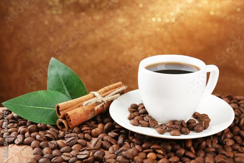 kawowe-fasole-i-filizanka-kawy-na-stole-na-brown-tle