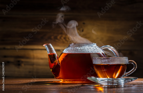 Poster The glass teapot and mug on the wooden background