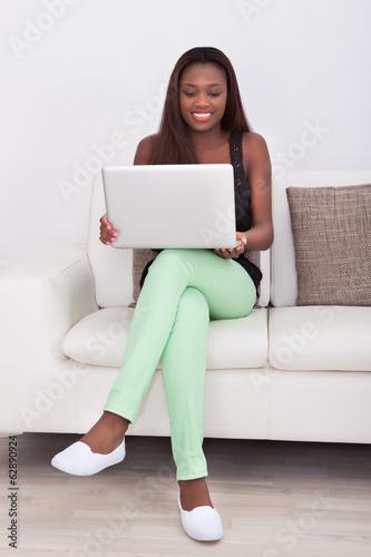 Fototapeta Young woman using laptop while sitting on sofa in living room obraz na płótnie