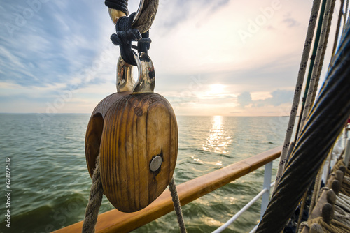 Photo Stands Ship Wooden pulley on an old yacht. Sunset