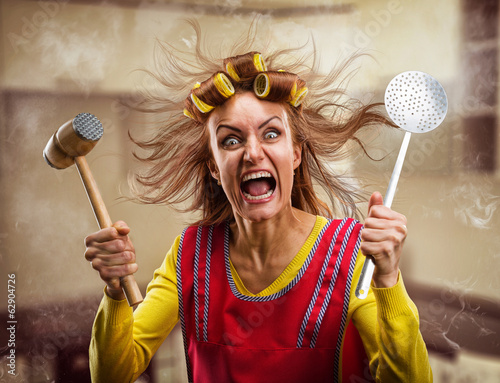 Crazy housewife with hammer on her hand Canvas Print
