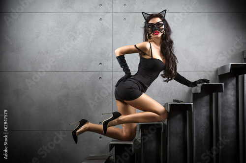 Fotografía sexy woman in catwoman suit lying on stairs