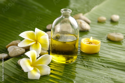 Staande foto Spa frangipani and stones with yellow candle on wet banana leaf