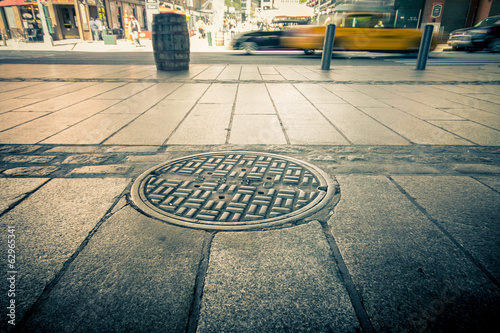 Poster New York TAXI Manhole drain cover on streets of lower Manhattan