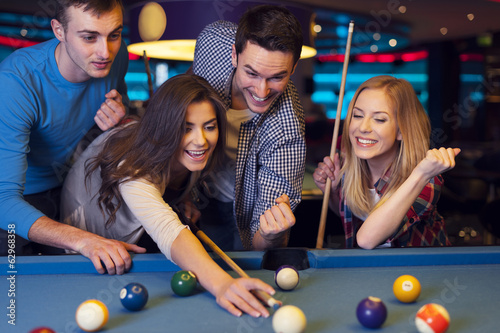 Fotografie, Obraz  Friends cheering while their friend aiming for billiards ball