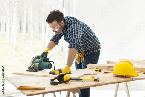 Obraz Carpenter cutting plank by circular saw - fototapety do salonu