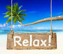 Wooden Sign With Relax Hanging On Beach