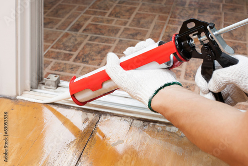 Foto Worker applies silicone caulk on the wooden floor for sealant wa