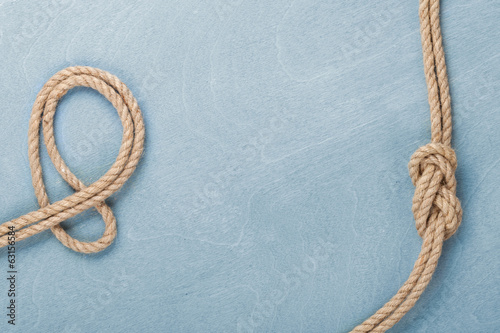 Poster Oceanië Ship rope knot on wooden texture background