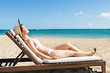 Woman Sunbathing On Deck Chair At Beach