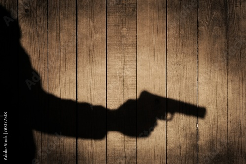 Plakát  Outstretched arm with a gun. Black shadow on wooden background.