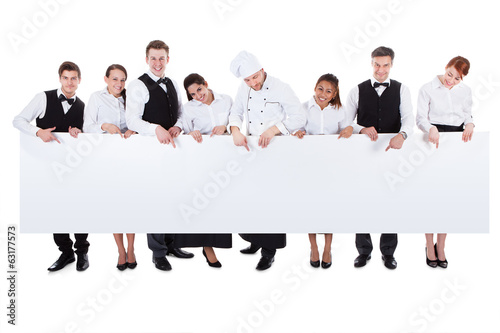 Fotografie, Obraz  Group of catering staff holding a blank banner