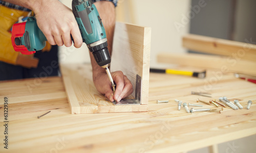 Obraz Close up of carpenter working with drill - fototapety do salonu